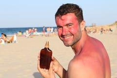 Sunburned man using tanning accelerator lotion.  stock photos