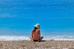 Sunburned young woman sitting at seashore Stock Photo