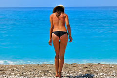 Sunburned young woman standing at seashore Royalty Free Stock Photography