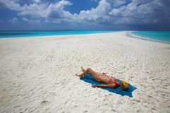 Sunburning on the sandy beach. Young women is sunburning on the infinity coral sandy beach Royalty Free Stock Photo
