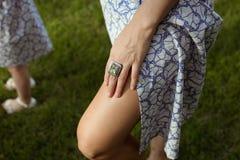 Sunburnt πόδια γυναικών στο θερινά ύφασμα και το χέρι στοκ εικόνα