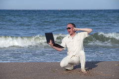 Sunburnt man with phone and laptop. Sunburnt businessman working with laptop and phone on a beach Stock Photography