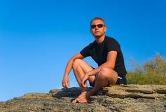Sunburnt man seats on rock Royalty Free Stock Photos
