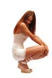 Sunburnt model in white dress. Sunburnt model in white short dress and slim legs bound squats edgeways Royalty Free Stock Photos