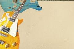 Sunburst лимона и голубая электрическая гитара на светлой предпосылке кожи, с множеством космоса экземпляра Стоковые Фото