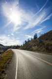 Sunburst above an empty tarred road. In forested mountainous terrain royalty free stock photos