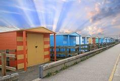 Sunburst beach huts. Photo of beach huts on the kent coast of whitstable with sunburst sun rays sky Royalty Free Stock Photography