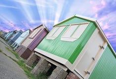 Sunburst beach huts. Photo of beach huts with sunburst sun rays through the clouds Royalty Free Stock Image