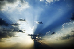 Sunburst in blue sky. With beams shining through the clouds Royalty Free Stock Image