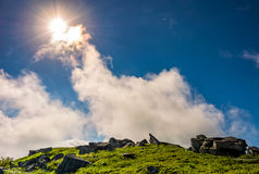 Sunburst on a blue sky with clouds over the mountains. With rocky hillside Stock Photos