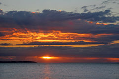Sunburst through clouds sunset Stock Images