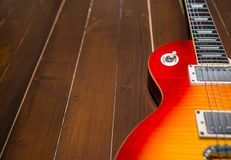 Sunburst elektrisk gitarr på trägolvslut upp royaltyfria bilder