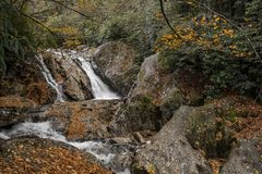 Sunburst Falls. North Carolina. Beautiful cascading waterfall right along NC 215 just a few miles north of the Blue Ridge Parkway. Seen here with autumn colors royalty free stock photos