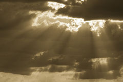 Sunburst of golden light beams shining through clouds Stock Image