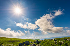 Sunburst på en blå himmel med moln över bergen royaltyfri fotografi