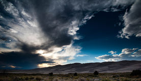 Sunburst and Sand Dunes. Sun bursting out of the clouds over the sand dunes and fields of Great Sand Dunes National Park in southern Colorado Royalty Free Stock Photos