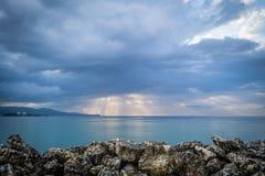 Sunburst till och med hällregnmoln på solnedgången Montego Bay, Jamaica royaltyfria foton