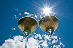 Sunburst Wine. Closeup of two wineglasses with a sun burst filled with white wine side by side with bright blue sky & clouds in the background Stock Image