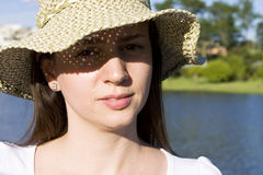 Suncare. Young woman using a hat to protect from the sun royalty free stock images