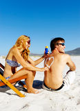 Suncare beach couple. Girlfriend playfully draws a heart on her boyfriends back with spf sunblock on summer vacatibon Royalty Free Stock Photography