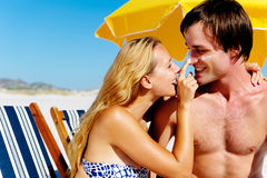 Suncare couple. Summer beach couple take care of their skin with sunblock lotion of high SPF for maximum protection Stock Photography