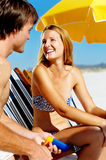 Suncare couple. Summer beach couple take care of their skin with sunblock lotion of high SPF for maximum protection Stock Photos