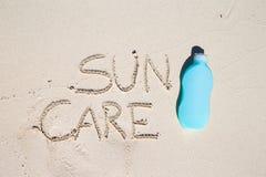 Suncare scritto sulla sabbia bianca tropicale e Immagini Stock