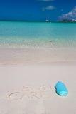 Suncare scritto sulla sabbia bianca tropicale e Fotografia Stock