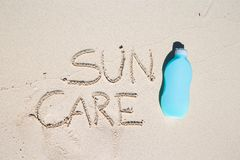 Suncare written on tropical white sand and. Suncare written on tropical beach white sand and suncream Stock Images