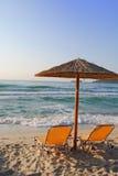 Sunchair och paraply på den grekiska stranden Royaltyfria Foton