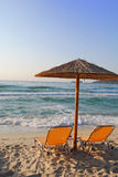 Sunchair and umbrella on Greek beach. Beach umbrella and two chairs at the beach Royalty Free Stock Photos