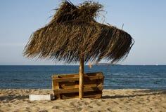 Sunchair und Regenschirm auf dem Strand stockbild