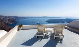 Sunchairs, das den Kessel von Santorini gegenüberstellt Stockfoto