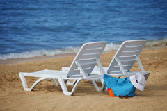 Sunchairs e borsa imballata della spiaggia sulla spiaggia di sabbia vuota Fotografia Stock