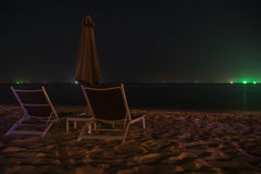 Sunchairs. In the night with umbrella on the beach Royalty Free Stock Photos