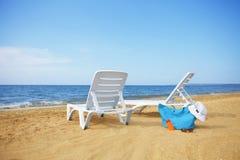 Sunchairs och packad strandpåse på den tomma sandstranden Royaltyfri Bild
