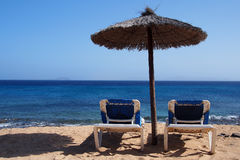 Sunchairs onder een paraplu bij tropisch strand Stock Afbeelding