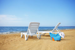 Sunchairs and Packed beach bag on empty sand beach Royalty Free Stock Image