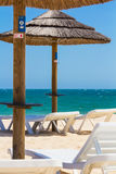 Sunchairs and parasol. Sunchairs and two parasols on a beach, close to the sea Stock Photo
