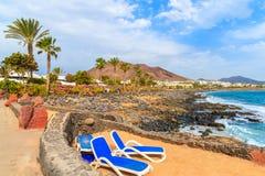 Sunchairs on Playa Blanca beach. In mountain landscape of Lanzarote island, Spain Royalty Free Stock Image