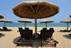 Sunchairs and umbrellas on the beach Stock Image