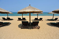Sunchairs and umbrellas on the beach Stock Photography