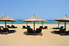 Sunchairs and umbrellas on the beach. Located in  Sanya, Hainan, China Royalty Free Stock Photos