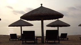 Sunchairs and umbrellas on the beach. Sea at sunrise, located in Sanya,Hainan,China stock video