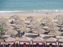 Sunchairs und Regenschirme auf Strand Stockfotografie