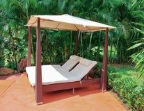 Sunchairs under sunshade in garden Royalty Free Stock Photography