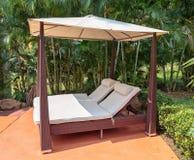 Sunchairs under sunshade in  tropical garden. Sunchairs under sunshade in a tropical garden Royalty Free Stock Photo