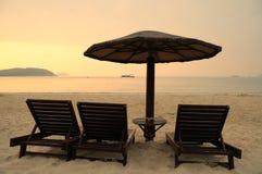 Sunchairs y paraguas en la playa en la salida del sol Imágenes de archivo libres de regalías