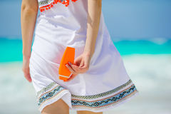 Suncream bottle in female hands background the sea. Suncare concept. Royalty Free Stock Photography