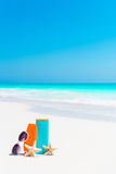 Suncream bottles, goggles, starfish and sunglasses on white sand beach background ocean Royalty Free Stock Photos